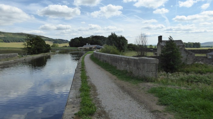 Image shows the canal crossing Holme Bridge Aqueduct with a footpath alongside