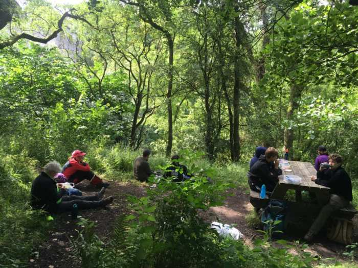 Young Ranger sit down at benches in woods beneath the viaduct to enjoy their lunch