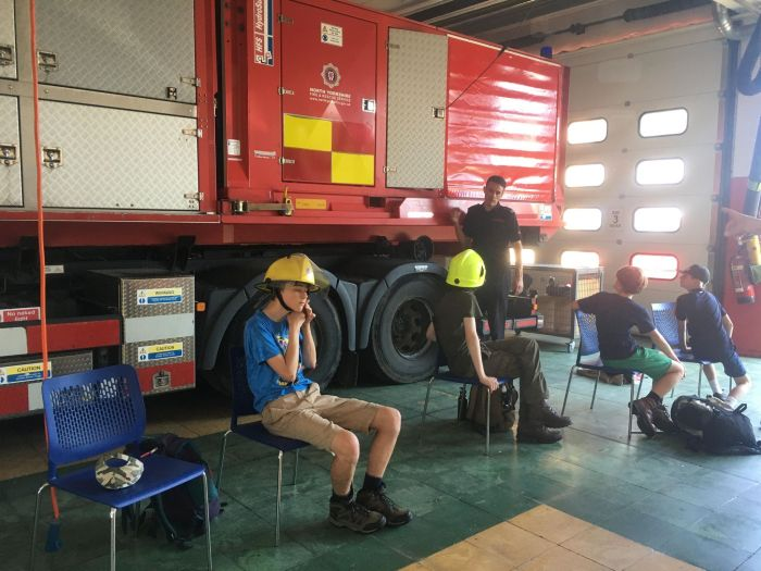 Young Rangers sit down on chairs inside the Fire Station, whilst listening to a firefighter talk about the station.