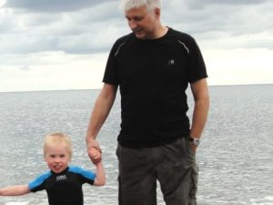 Martin holding his son Joel's hand on a beach in Northern Ireland