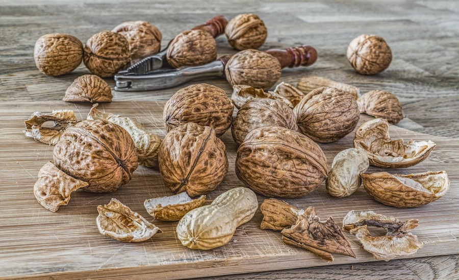Pile of walnuts with a nutcracker on a wooden surface