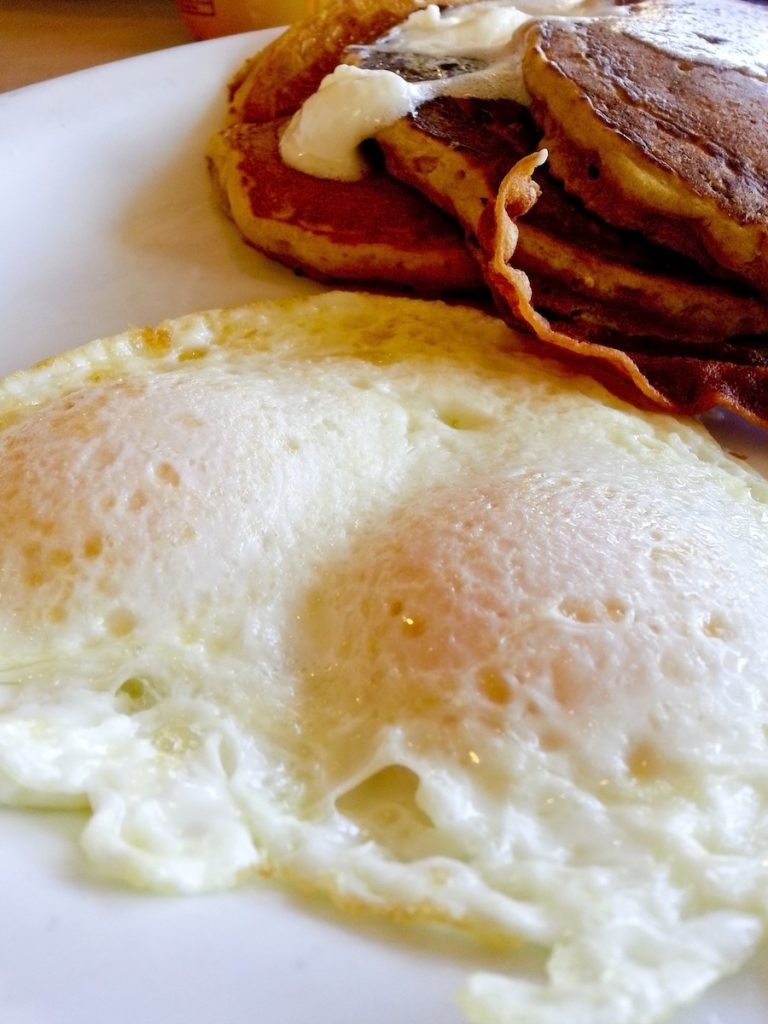 Eggs over easy on a white plate with slices of bacon