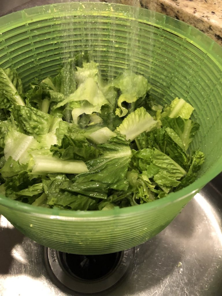 Chopped lettuce being rinsed in the strainer basket of a salad spinner
