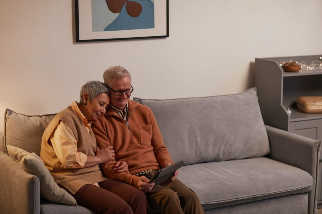older couple sitting on the couch with tablet