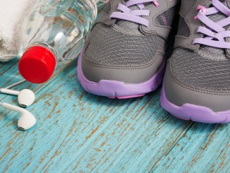 Workout set with sport shoes, earphones and drinking water on wood background