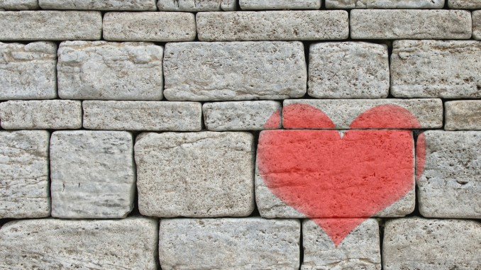 Pink heart painted on grey stone wall
