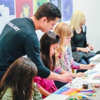 art teacher with paint brush teaching students during studio lesson