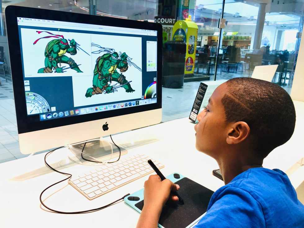 art student on iMac computer drawing a cartoon character in green