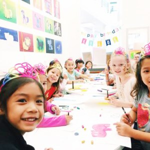 Group of girls gather around a table for a birthday party