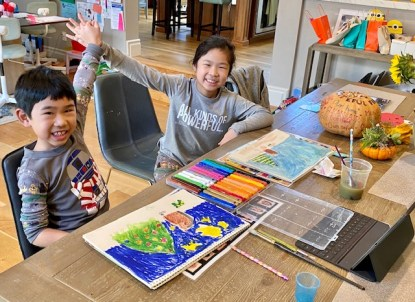 2 students smiling and giving each other a high five. art supplies on table in front of them