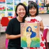 student and teacher holding art creation canvas 11x14