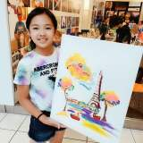 student holding 16x20 canvas with painting