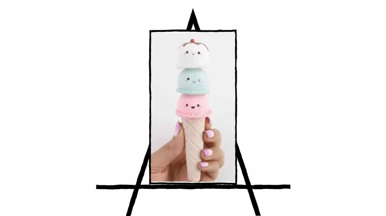 image of hand holding an ice cream cone with 3 scoops of ice cream with faces