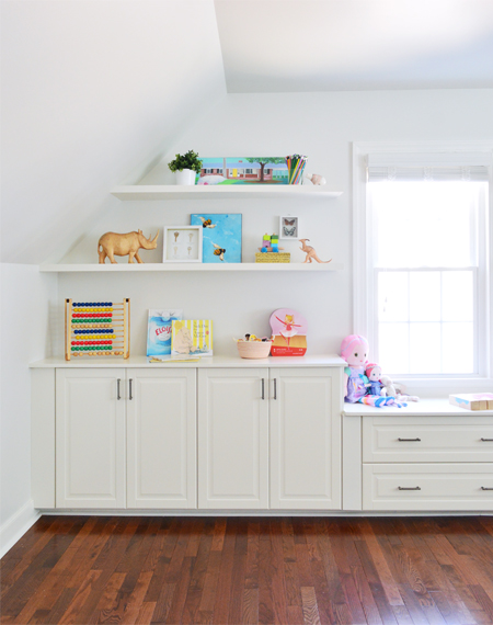 Two white floating shelves styled nicely with cheerful kids games and toys above white Ikea cabinets