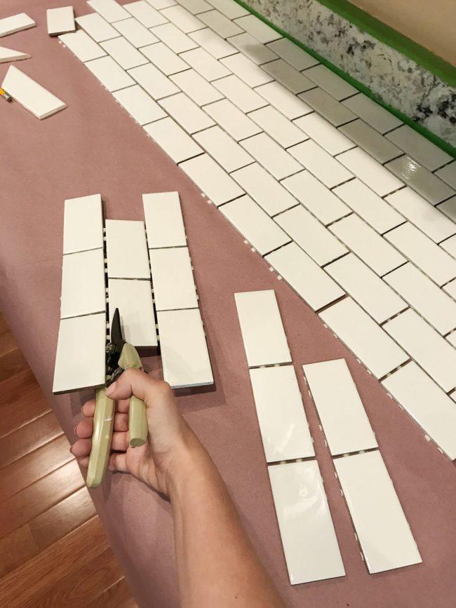 Sherry using scissors to cut tiles off subway tile sheet