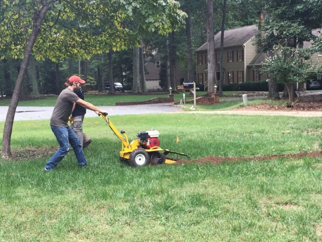using trencher tool to dig irrigation system in front yard