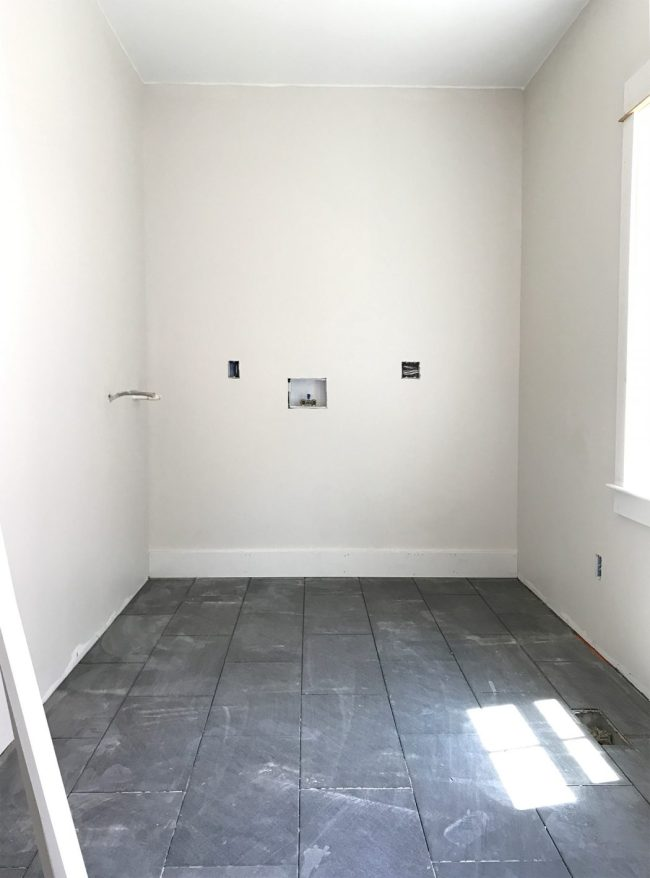 laundry room area after drywall paint and dark slate tile
