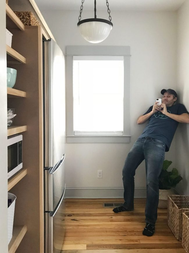 John leaning awkwardly against wall trying to take a photo of pantry shelves
