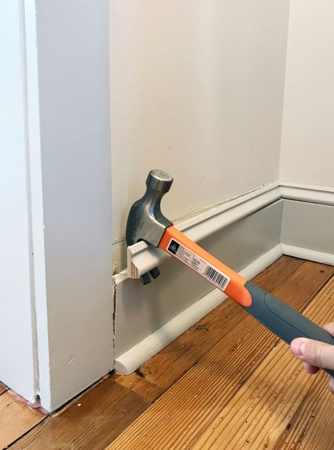 hammer prying off baseboard molding in pantry