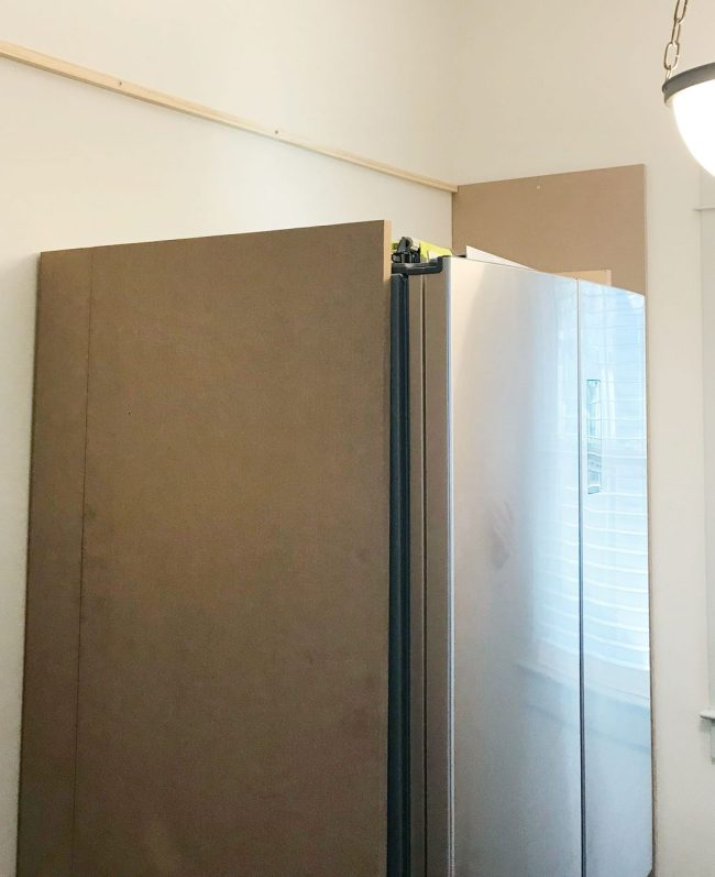 large MDF pieces added vertically against fridge in pantry