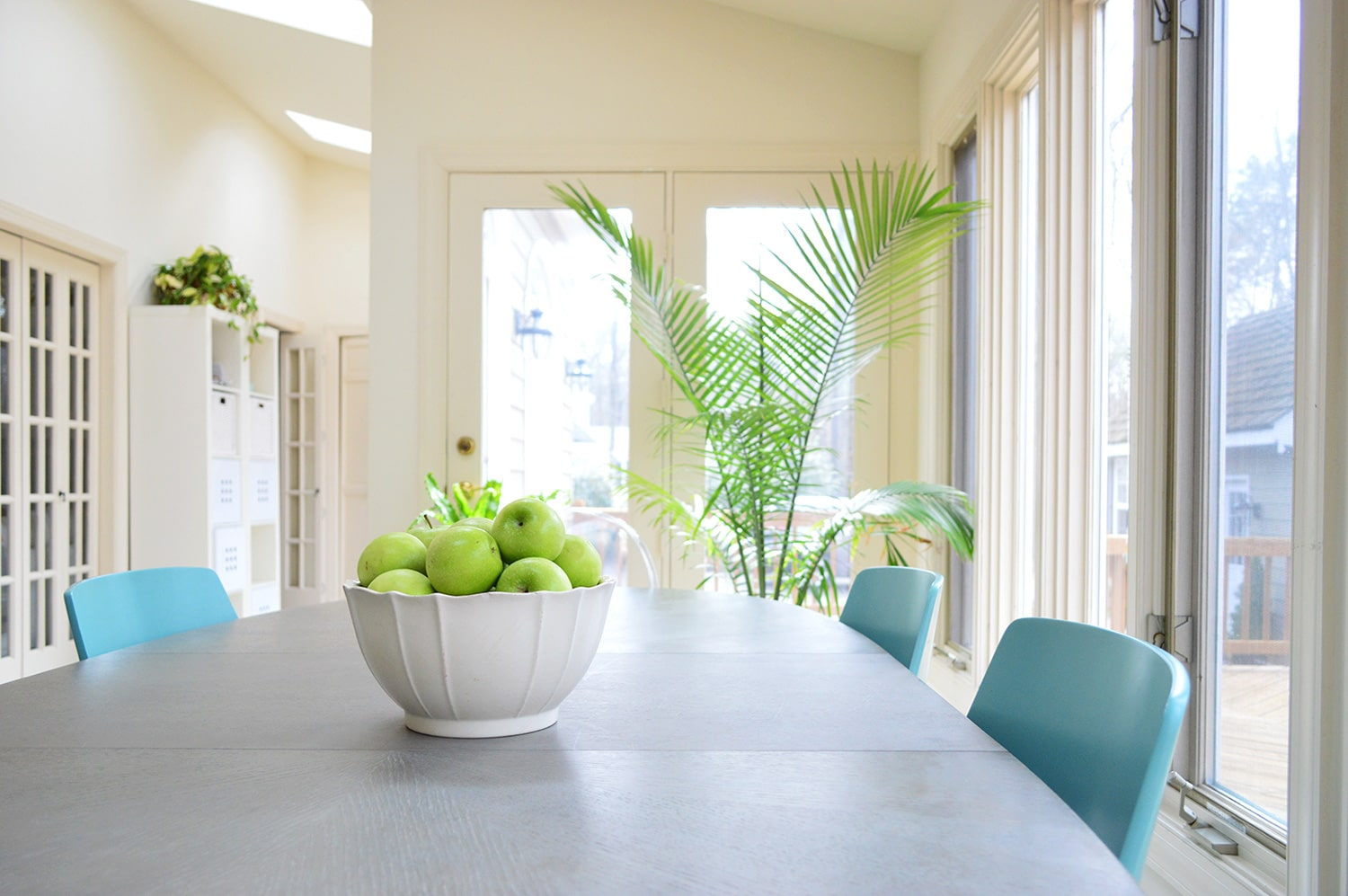 gray breakfast table with bowl of green apples on it