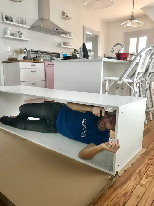 john laying in ikea cabinet during assembly