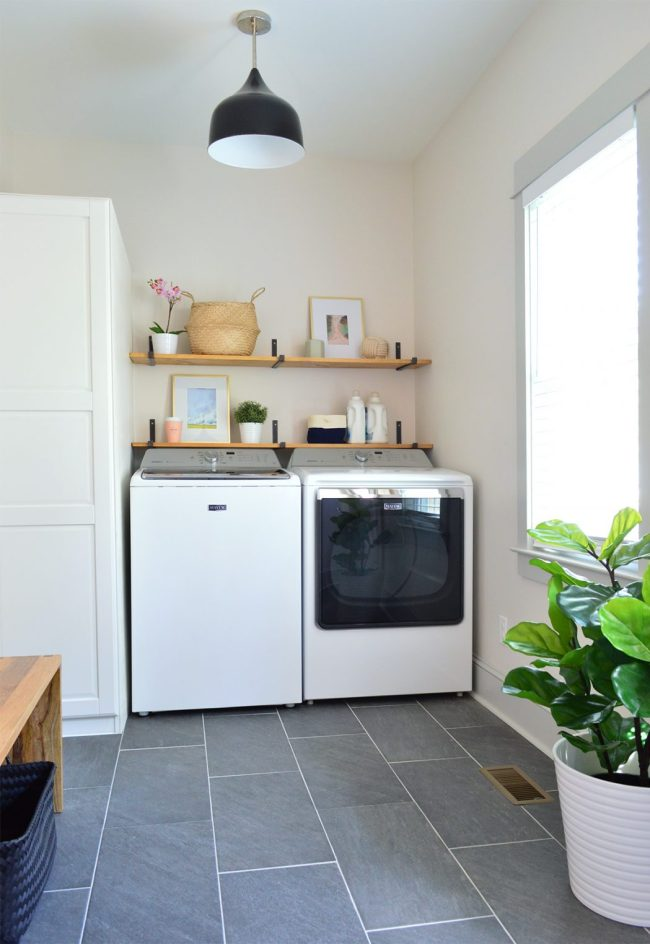 laundry room with slate floors black light fixture open wood shelves