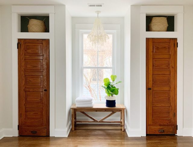 Faux fiddle leaf fig on bench between two closets under chandelier