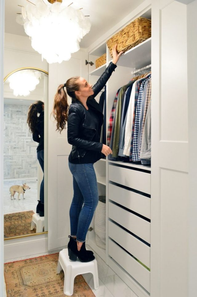 Sherry Standing On Stool In Master Closet To Reach Top Shelf