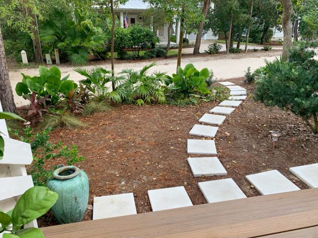 Pathway Of Square White Pavers Around Tropical Plantings