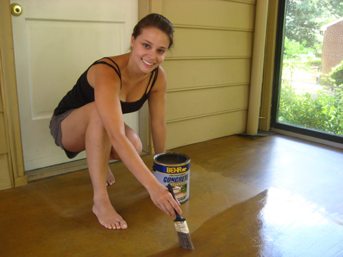 applying Behr Semi-Transparent Concrete Stain to concrete floor using a paintbrush