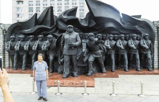 A Chinese tourist poses in front of a statue of PLA general Peng Dehuai on Dandong's Broken Bridge.