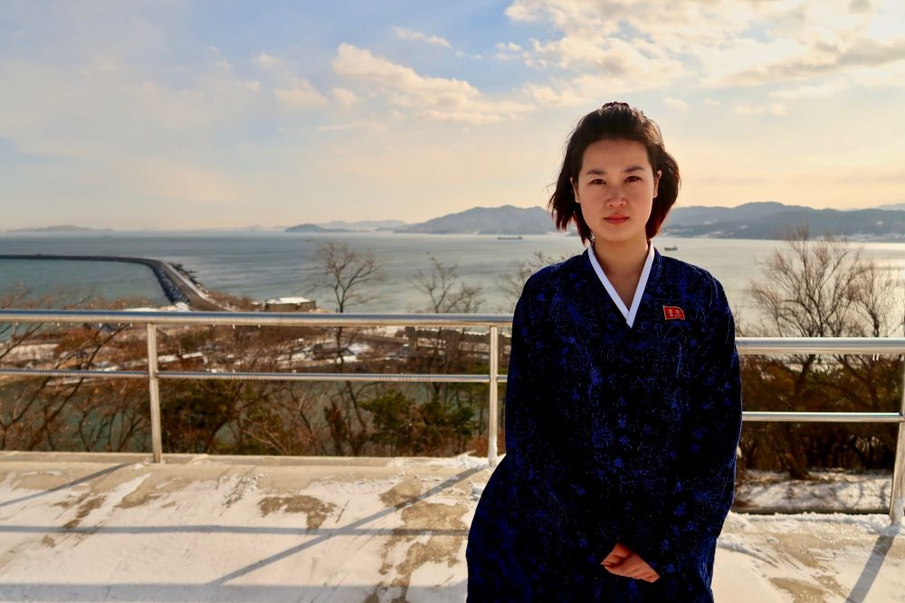 A young North Korean woman in a traditional Hanbok dress poses in front of the Nampo West Sea Barrage.