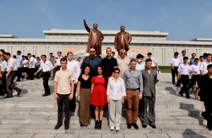 A group of tourists pose in front of the Mansudae statues of Kim Il Sung and Kim Jong Il.