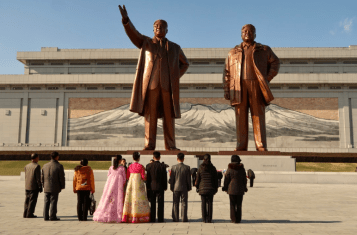 A group of Koreans regard the monuments of Kim Il Sung and Kim Jong Il at Mansudae Grand Monument.