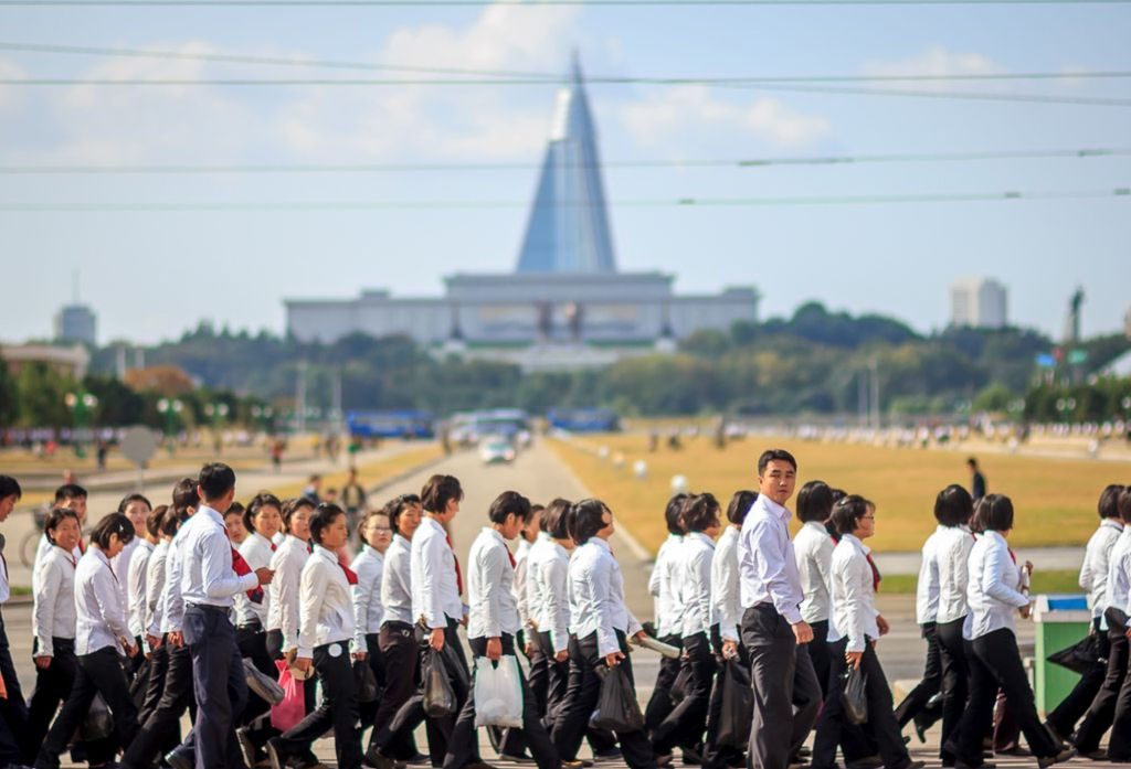 A group of North Korean students walk by the Mansudae statues where the Ryugyong hotel can be seen in North Korea
