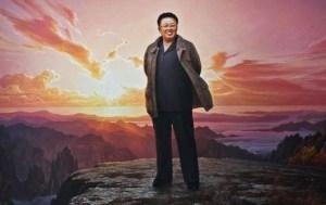 A large portrait of Kim Jong ll standing atop Mount Paektu at sunset.