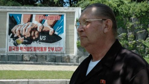 James Dresnok, an infamous North Korean celebrity, poses in front of an anti-US propaganda poster.