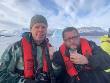 Two adventurers enjoy a beverage on their Greenland cruise.