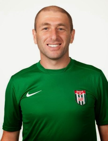 A smiling man with cropped hair poses in a green Abkhazia football jersey.
