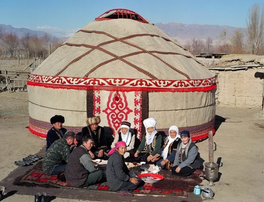A family poses in front of a steep-roofed Kyrgyz yurt.