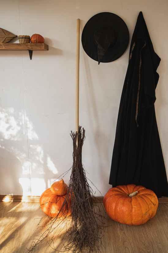 orange pumpkin beside black witch costume and a broom
