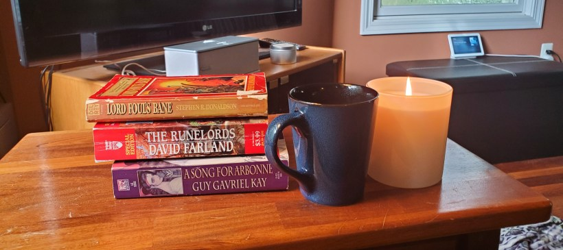 stack of books, candle, and coffee cup