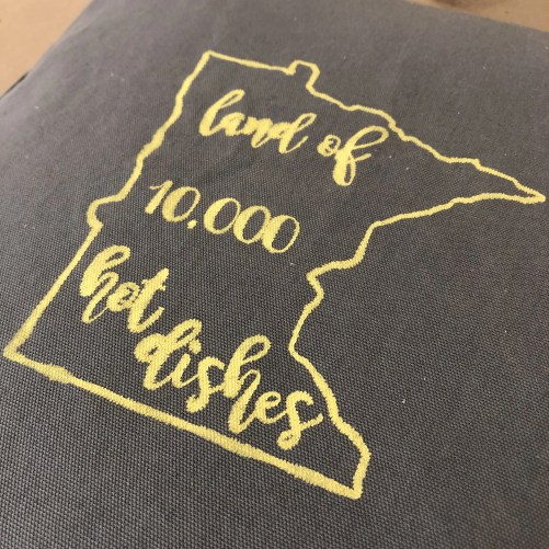 Pillow with the outline of the state Minnesota and the phrase land of 10,000 hot dishes inside