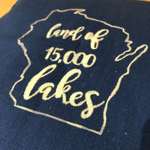 Pillow with the outline of the state of Wisconsin and the phrase land of 15,000 lakes inside
