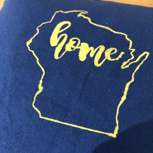 Pillow with the phrase home inside the outline of the state of Wisconsin.