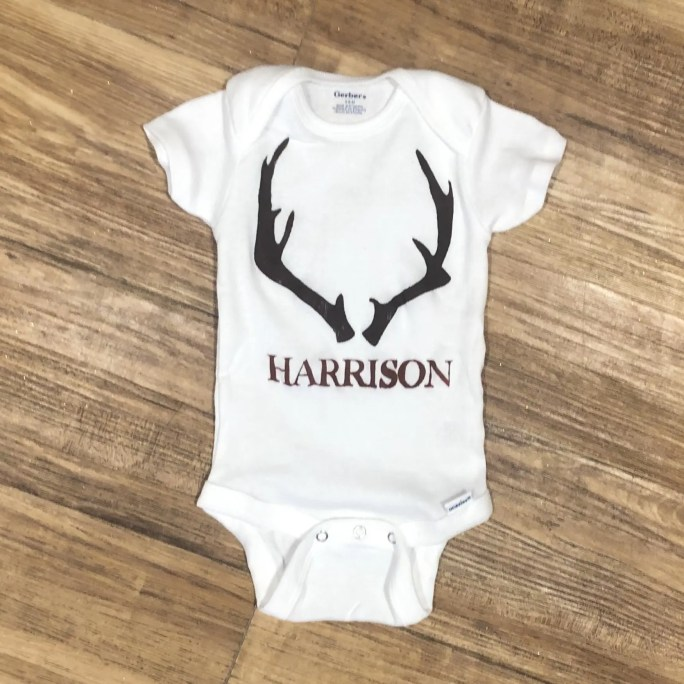 Baby onesie with a pair of antlers and the name Harrison below