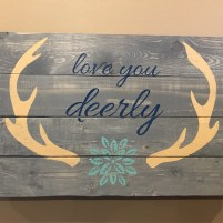 Wood pallet sign with the phrase love you deerly along with graphics of deer antlers and a flower.