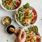 3 shrimp poke bowls in white bowls with a hand holding chopsticks and shrimp
