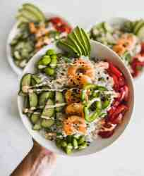 Shrimp poke bowl in the air with 2 other sushi bowls in the background